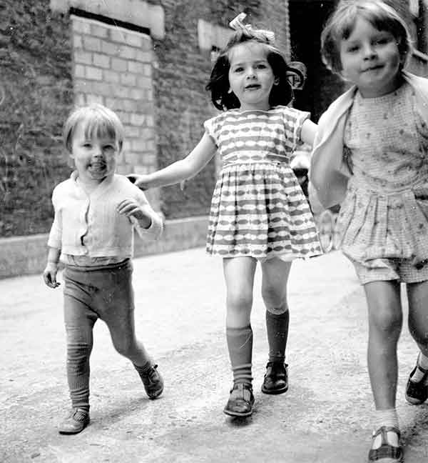 Two young girls and a boy playing in the street