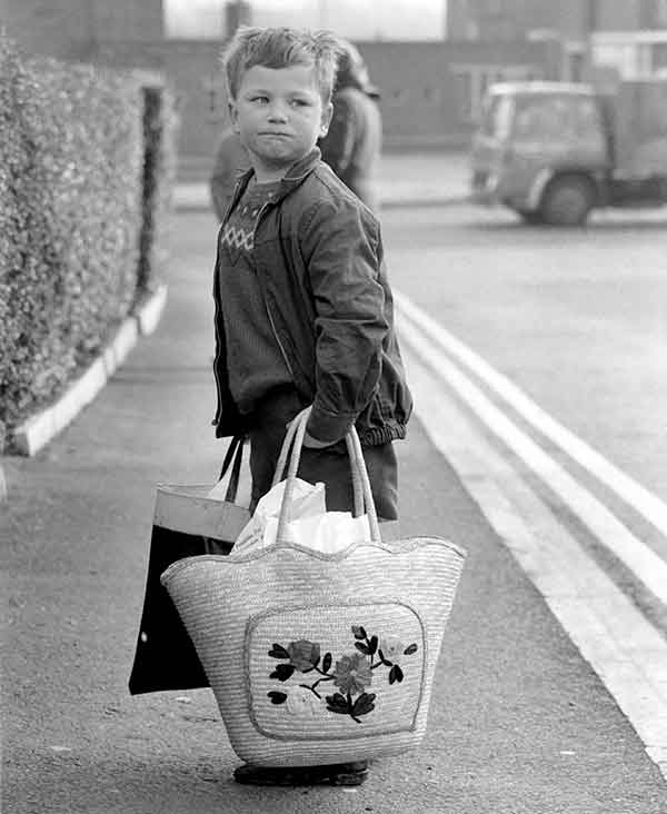 Young boy walking down the street holding heavy shopping bags