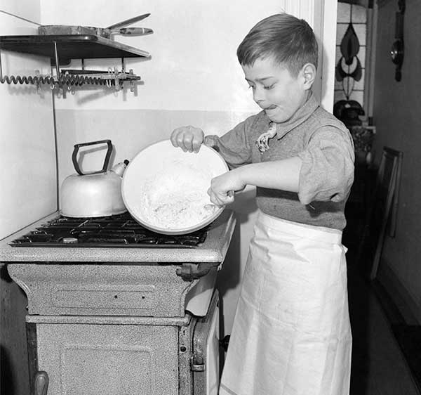 Young boy wearing an apron and washing up the dishes