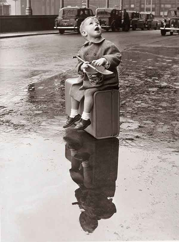 A child sat on a suitcase on edge of puddle clutching a spade