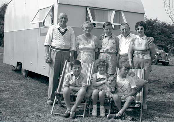 Family group posing for a photo outside their caravan