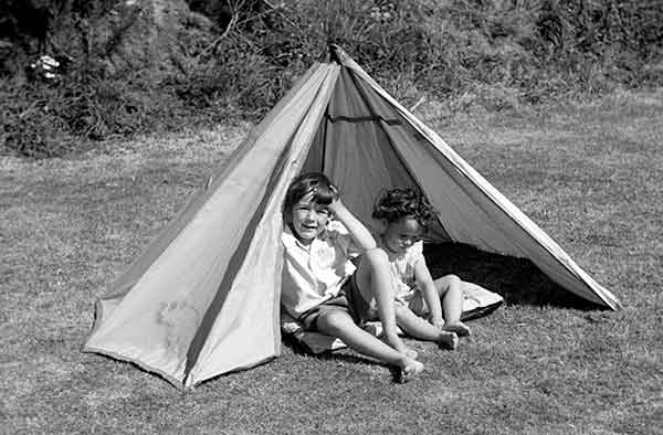 Two children sat in an old fashioned tent