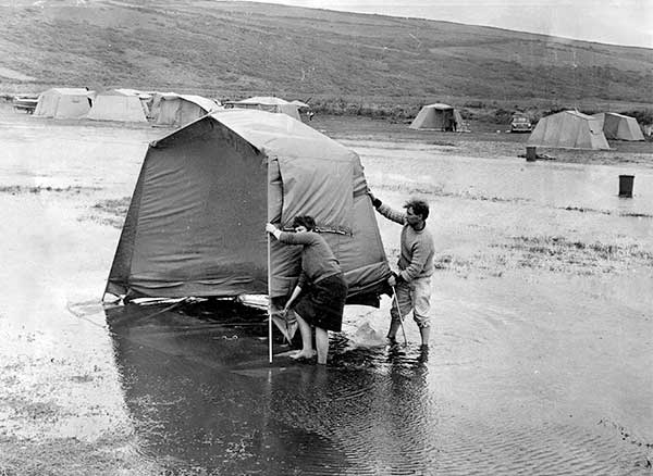 Two people holding onto a tent in the wind and rain