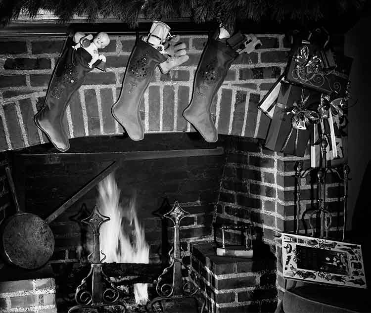 three stockings filled with presents hanging above a fireplace