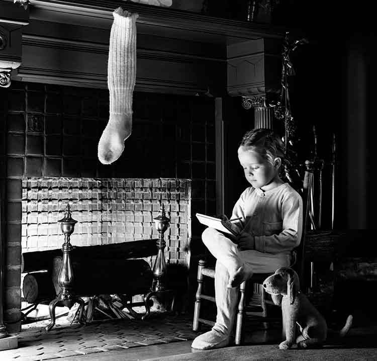 young child sitting by the fire writing a letter