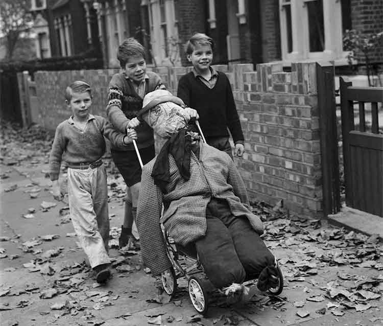 3 boys pushing a guy in a pram down the street