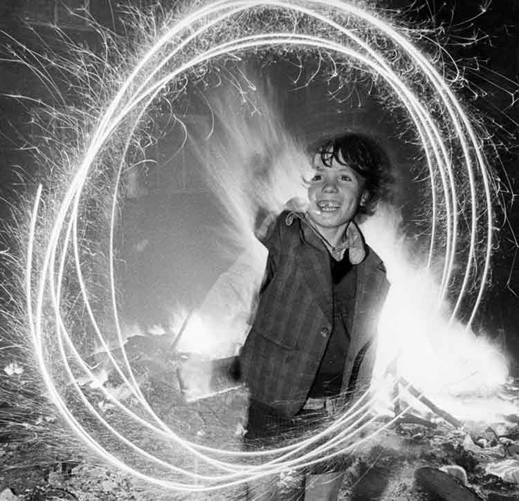 A delighted looking boy writing rings with a sparkler