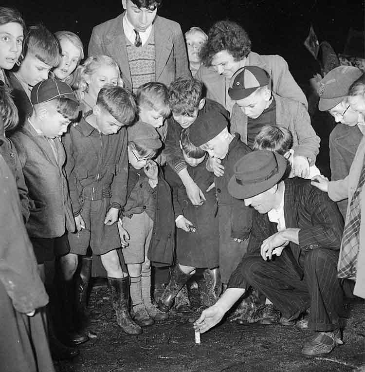 A man lighting a firework surrounded by children
