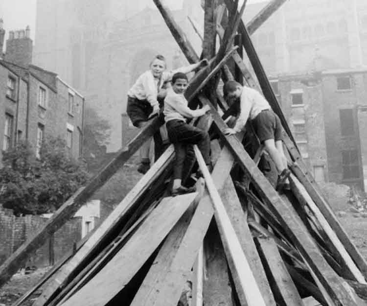 Group of children adding wood to a large bonfire