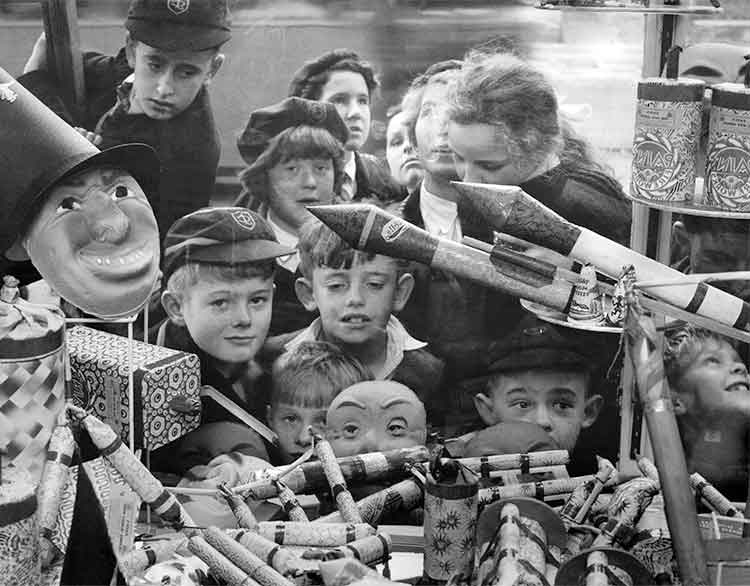 Group of children admiring a window display of fireworks