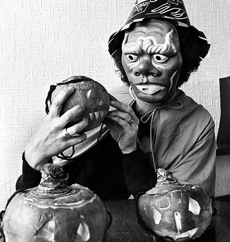 Person dressed as a witch holding a carved turnip