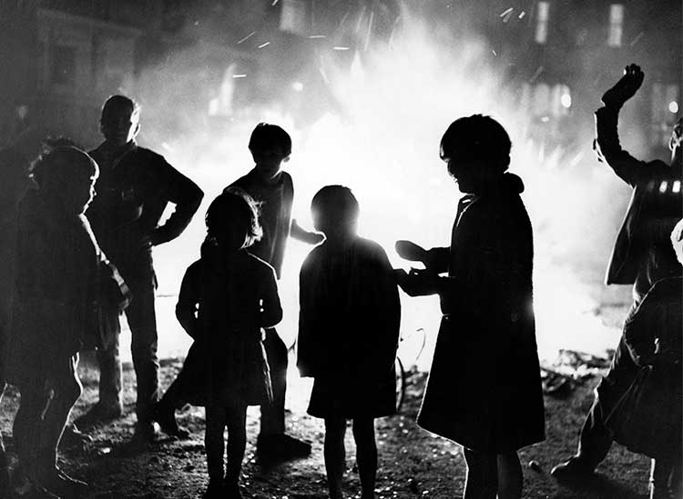 Silhouettes of children standing in front of a glowing bonfire