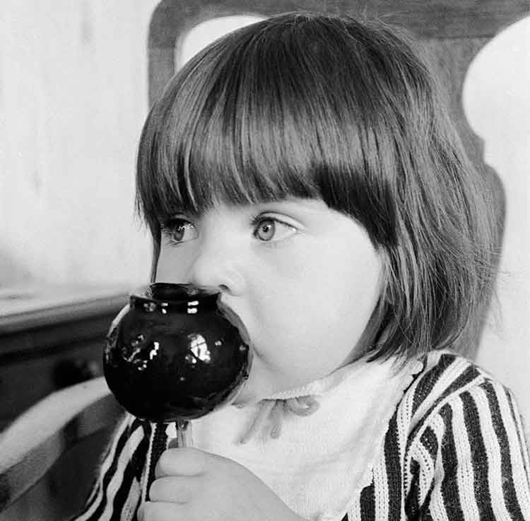 Young girl in striped dress eating a toffee apple