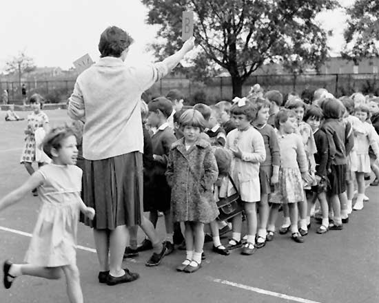 Children lined up in front of a teacher in the playground