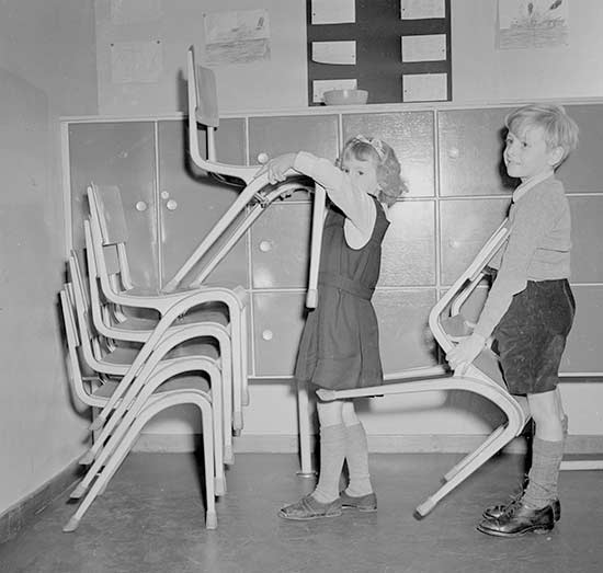 Young boy and girl stacking chairs after assembly