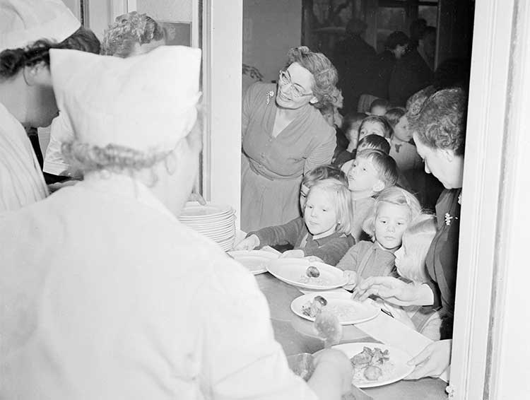 Dinner ladies serving food to a line of children