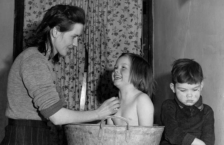Mum bathing her daughter in a tin bath
