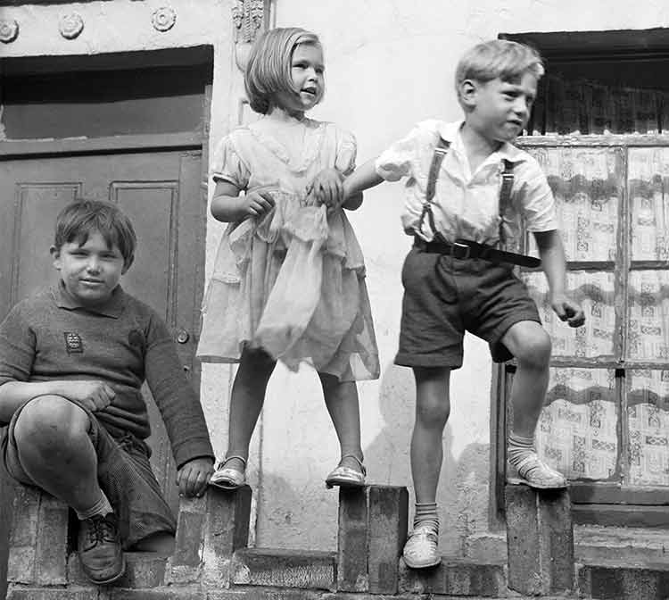 Three young children stood playing on a wall in front of a house