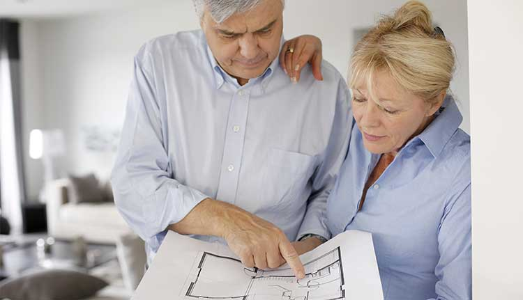 older couple looking at floor plans