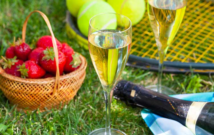 basket of strawberries and champagne on the grass