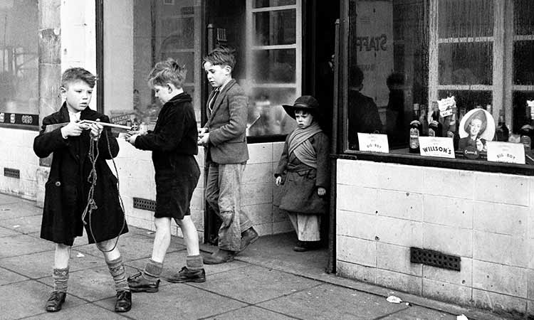 3 boys outside of a shop and one boy is holding a toy gun
