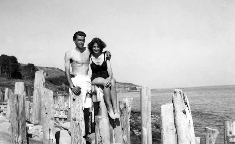 a young couple posing for a photograph by the sea