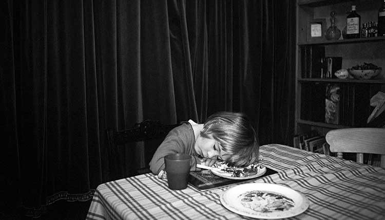 young girl asleep at the table with her in her plate of food