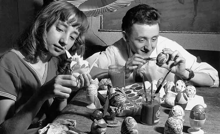 girl and boy painting eggs