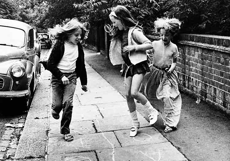 three young girls playing on the pavement