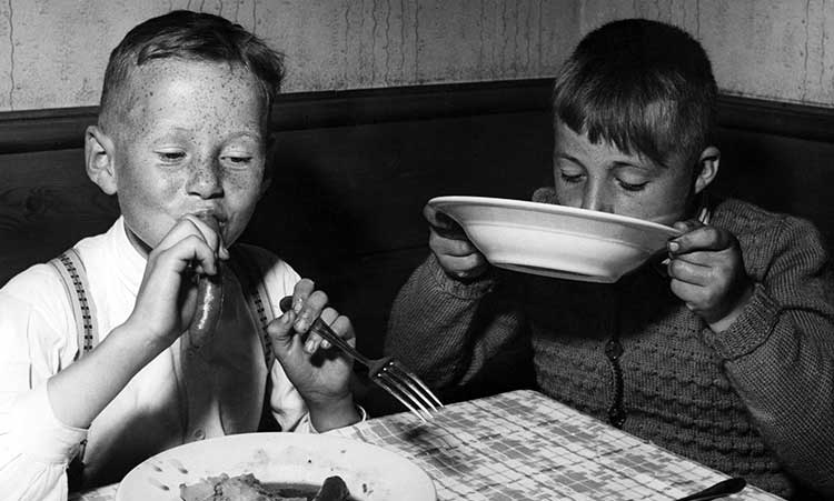 two young boys eating at the table