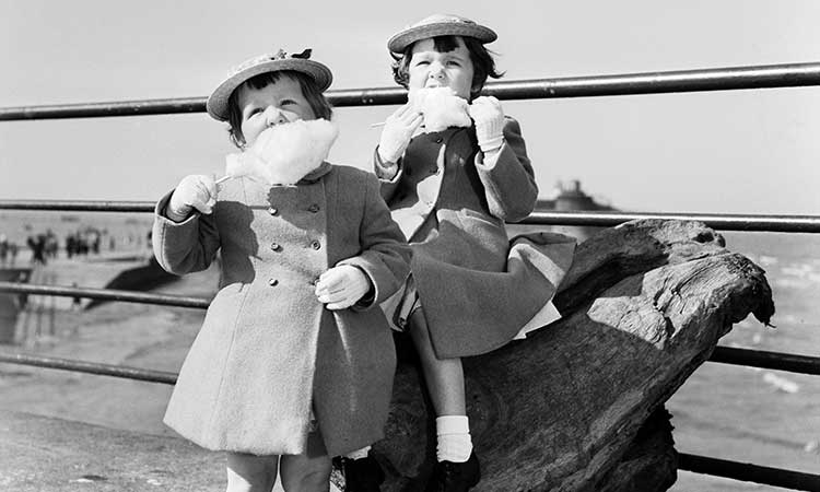 two young girls eating candy floss by the sea