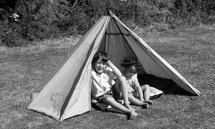young boy and girl sitting in a tent