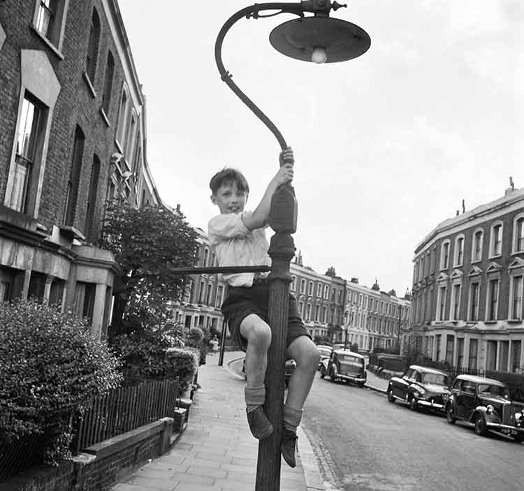 young boy hanging from a lamp post