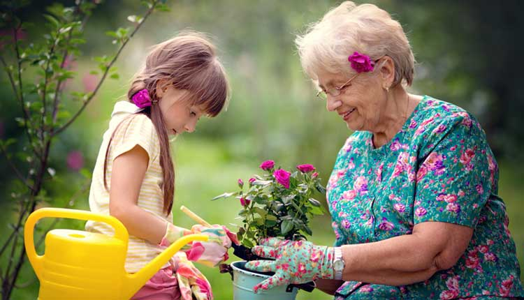 gran and granddaughter planting a flower
