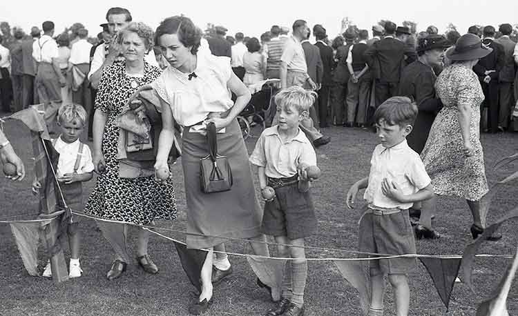 1950's mother with her two boys at a fete playing the game of throwing balls into a bucket to win a prize