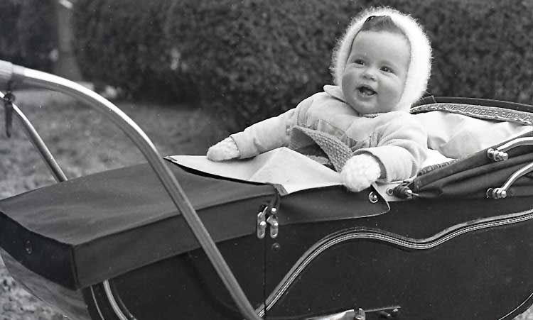 baby in a big coach pram wearing woolly hat while mum looks on