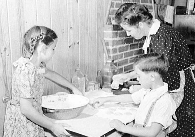 a girl with mixing bowl boy and mum baking on the kitchen table