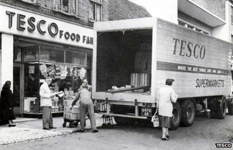 men unloading a van in front of a tesco store while shoppers walk by