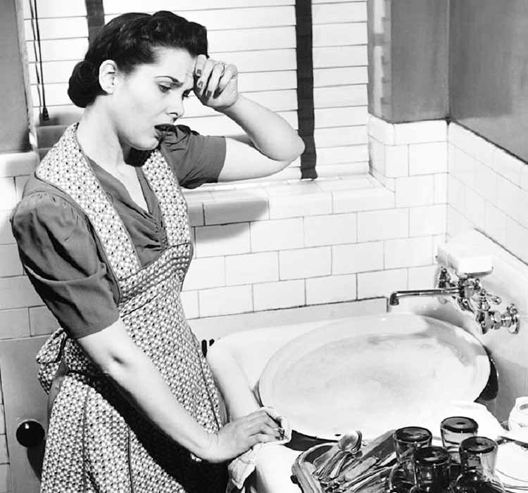woman with hand to head standing in front of a sink full of dishes