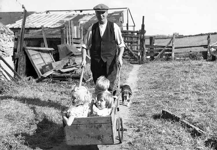 father pulling three young children in a wooden wheelbarrow