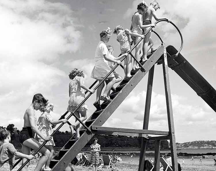 children on a slide at the beach