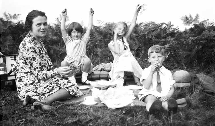 three children with their mum having a picnic