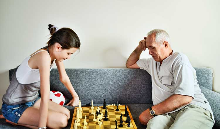 grandad and granddaughter playing a board game