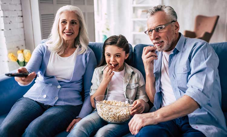grandparents watching a movie with their grandchild