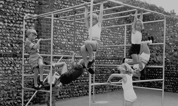 children doing gym on a metal climbing frame
