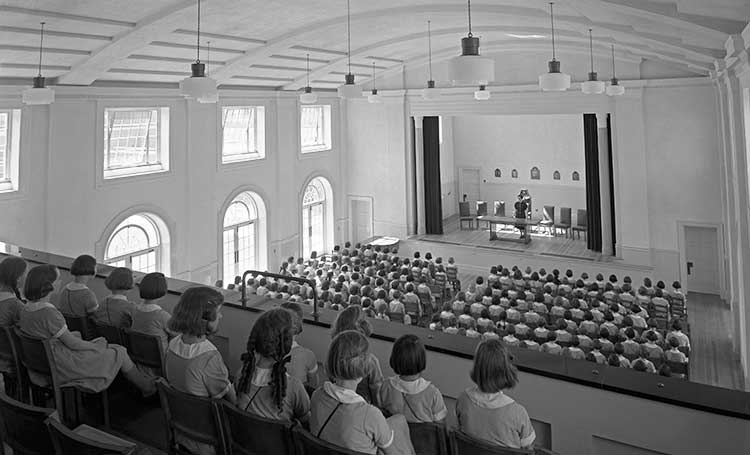 children sitting in a school assembly