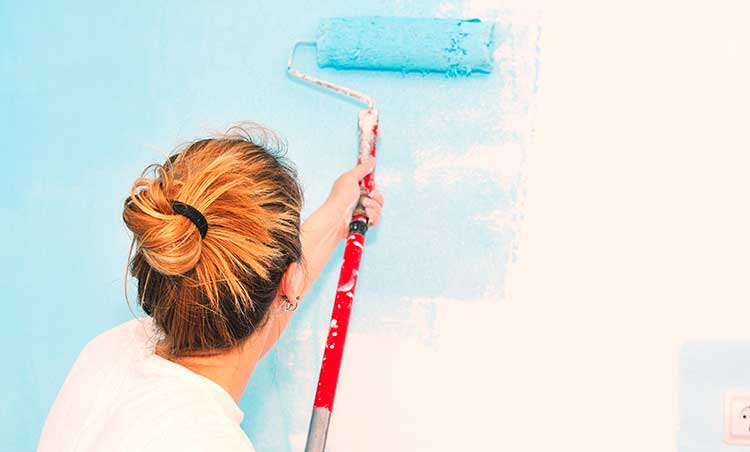 lady painting a blue wall