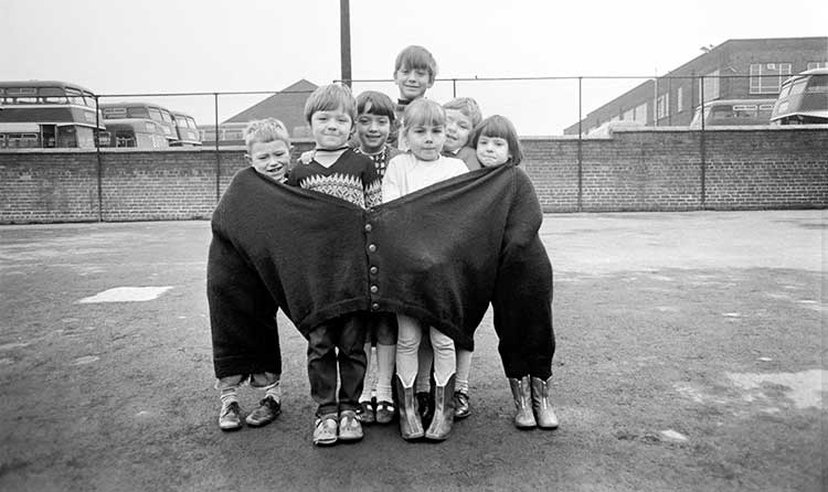 a group of children crammed into a large cardigan