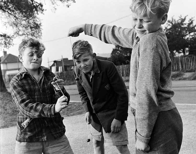 three boys playing conkers