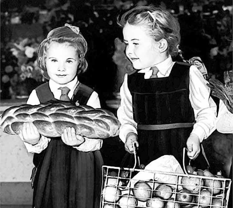two girls carrying food for the harvest festival